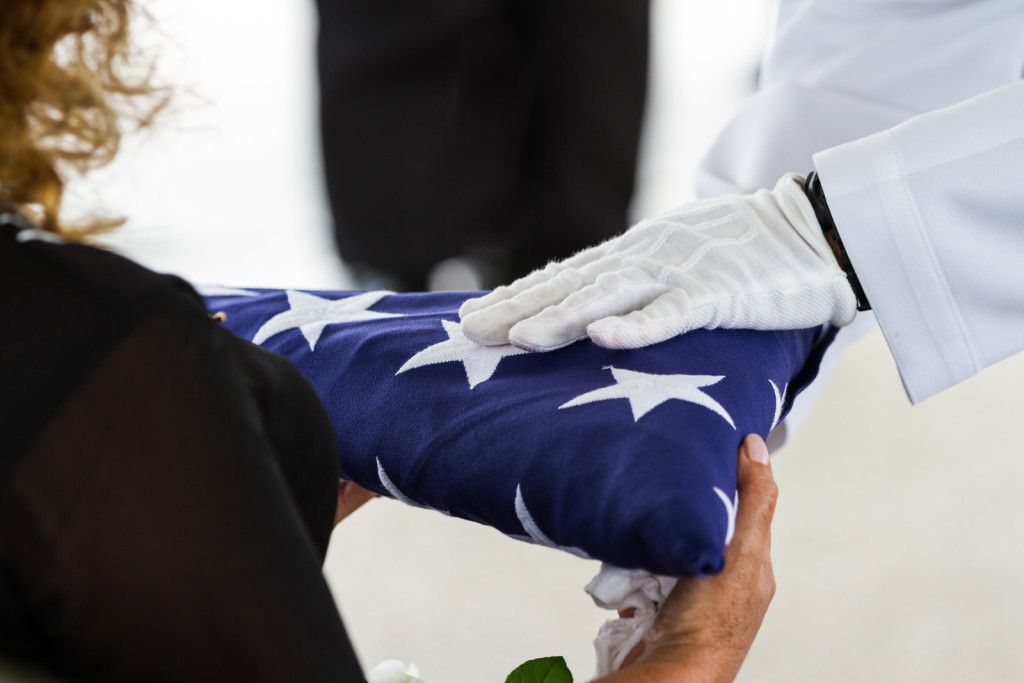 active navy representatives giving the US flag to the widow at a veterans funeral